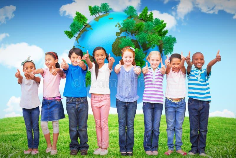 Imagen compuesta de los alumnos lindos que sonríen en la cámara en sala de clase fotografía de archivo