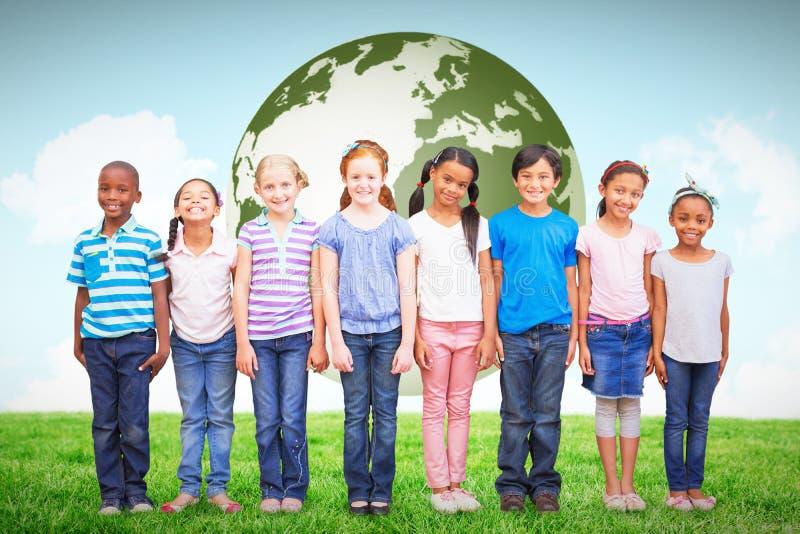 Imagen compuesta de los alumnos lindos que sonríen en la cámara en sala de clase imagen de archivo libre de regalías