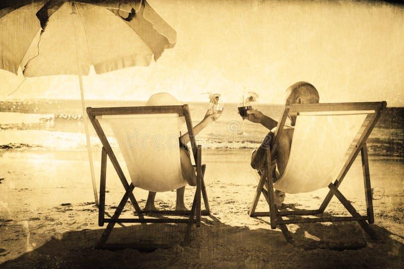 Imagen compuesta de los cócteles de consumición de los pares felices mientras que se relaja en sus sillas de cubierta libre illustration