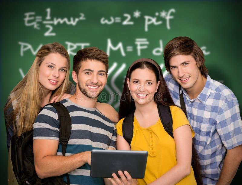 Imagen compuesta de los estudiantes que usan la tableta digital en el pasillo de la universidad fotos de archivo libres de regalías