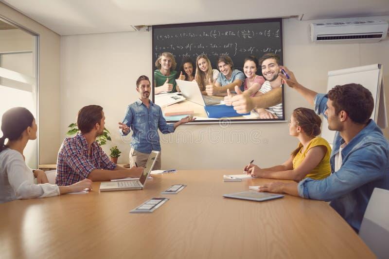 Imagen compuesta de los estudiantes universitarios que gesticulan los pulgares para arriba en biblioteca fotos de archivo