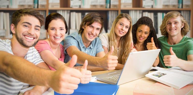 Imagen compuesta de los estudiantes universitarios que gesticulan los pulgares para arriba en biblioteca imagen de archivo libre de regalías