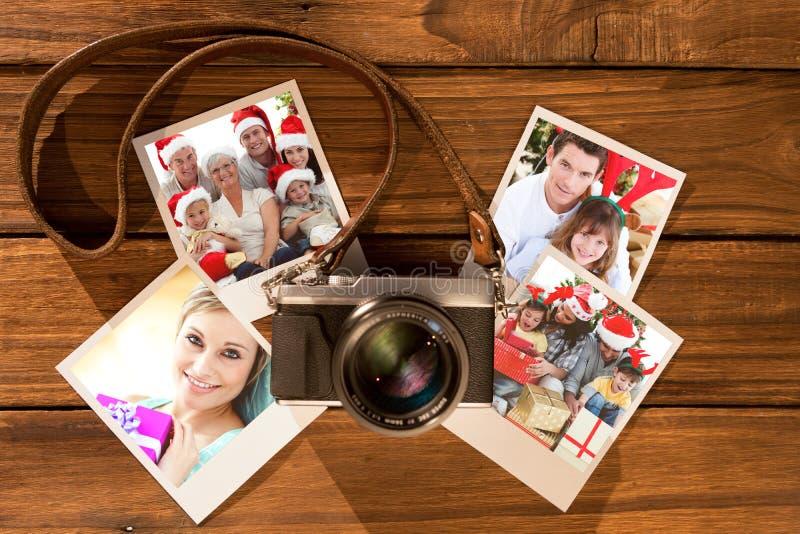 Imagen compuesta de los niños que se sientan con su familia que sostiene botas de la Navidad foto de archivo libre de regalías