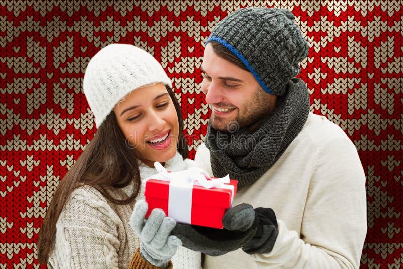Imagen compuesta de los pares del invierno que sostienen el regalo imagenes de archivo