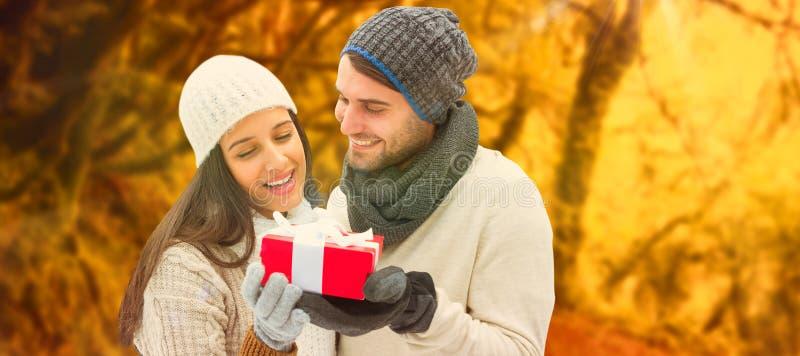 Imagen compuesta de los pares del invierno que sostienen el regalo imágenes de archivo libres de regalías
