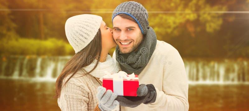 Imagen compuesta de los pares del invierno que sostienen el regalo fotos de archivo