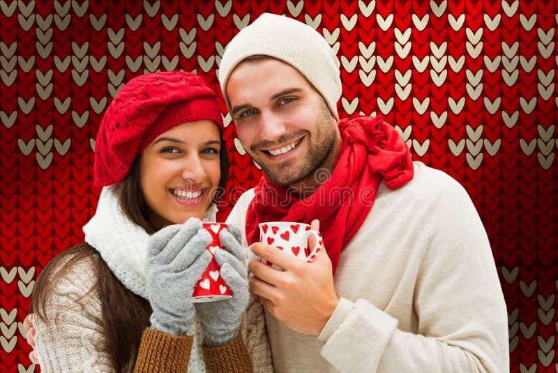 Imagen compuesta de los pares del invierno que sostienen las tazas foto de archivo libre de regalías