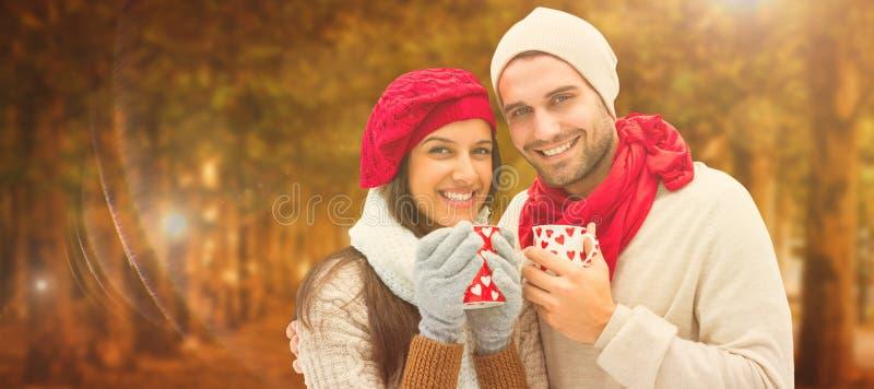 Imagen compuesta de los pares del invierno que sostienen las tazas fotos de archivo