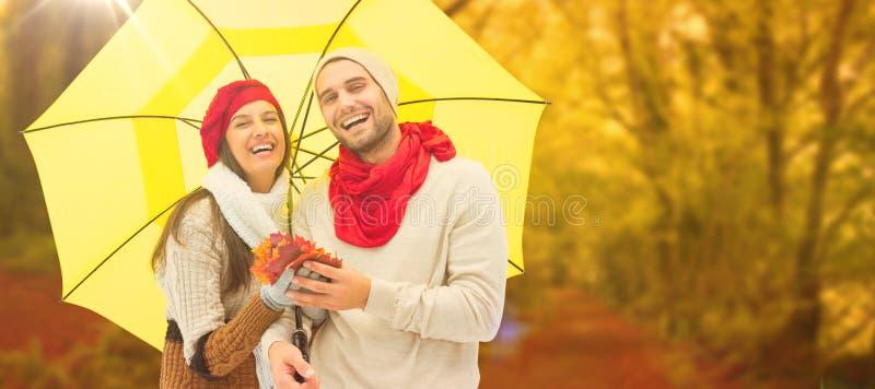 Imagen compuesta de los pares del otoño que sostienen el paraguas imagenes de archivo