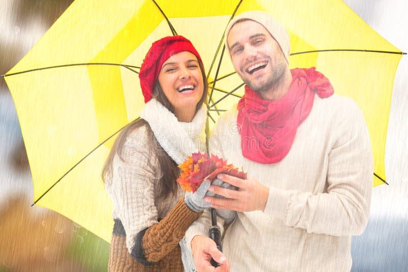 Imagen compuesta de los pares del otoño que sostienen el paraguas foto de archivo libre de regalías