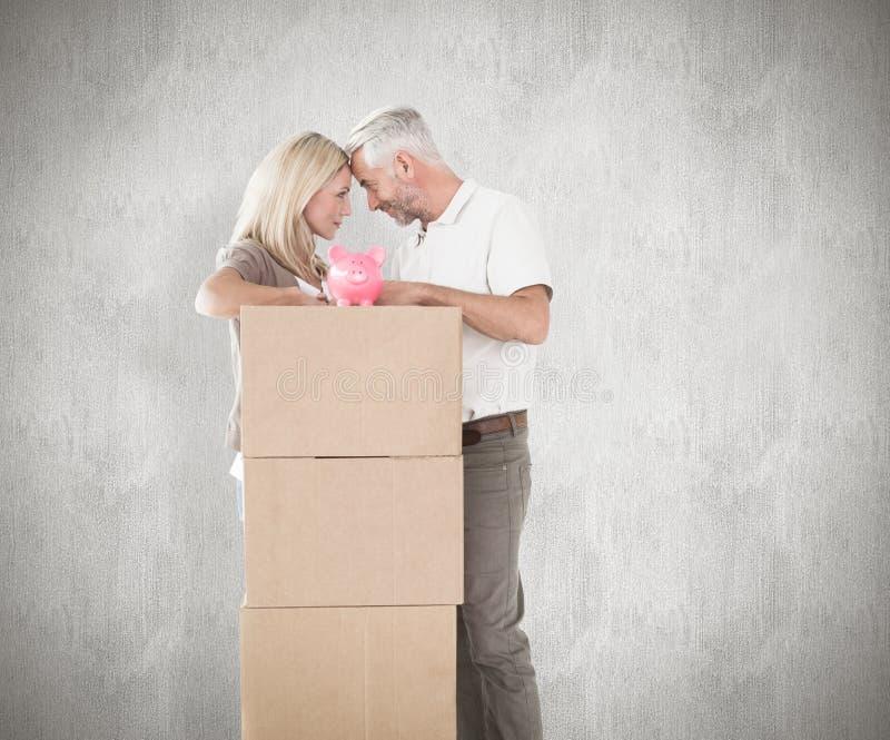 Imagen compuesta de los pares felices que se inclinan en la pila de cajas móviles con la hucha fotos de archivo