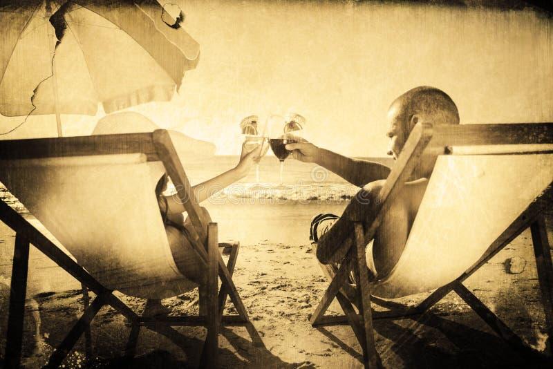 Imagen compuesta de los pares felices que tintinean sus vidrios mientras que se relaja en sus sillas de cubierta libre illustration