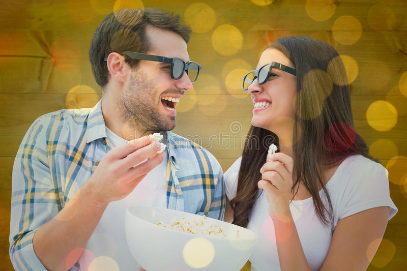 Imagen compuesta de los pares jovenes atractivos que miran una película 3d imagen de archivo libre de regalías