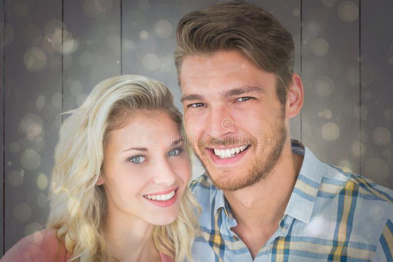Imagen compuesta de los pares jovenes atractivos que sonríen en la cámara foto de archivo