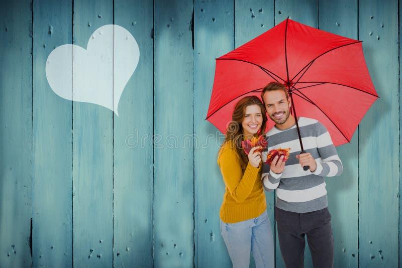 Imagen compuesta de los pares jovenes felices que sostienen el paraguas imágenes de archivo libres de regalías