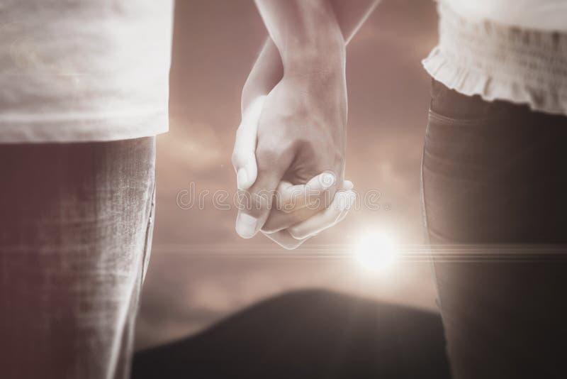 Imagen compuesta de los pares jovenes que llevan a cabo las manos en el parque imagen de archivo