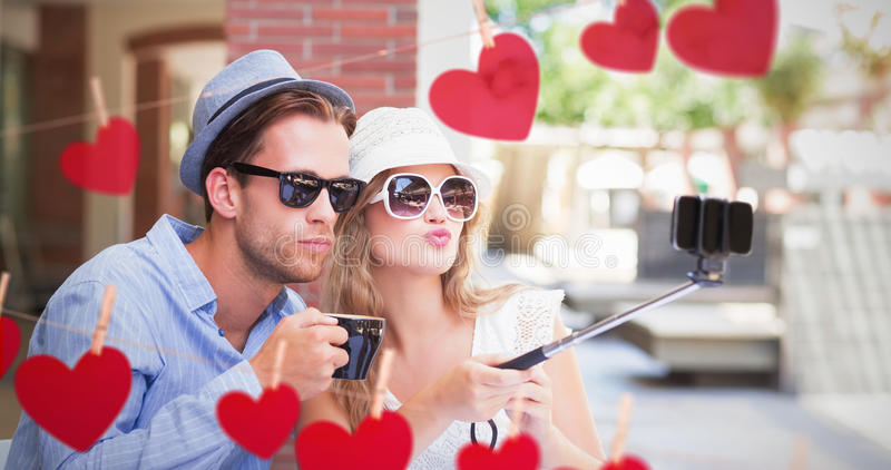 Imagen compuesta de los pares lindos que toman un selfie con el palillo del selfie imagen de archivo libre de regalías