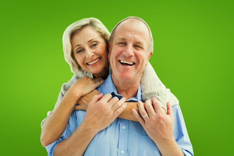 Imagen compuesta de los pares maduros felices que abrazan la sonrisa en la cámara imagenes de archivo