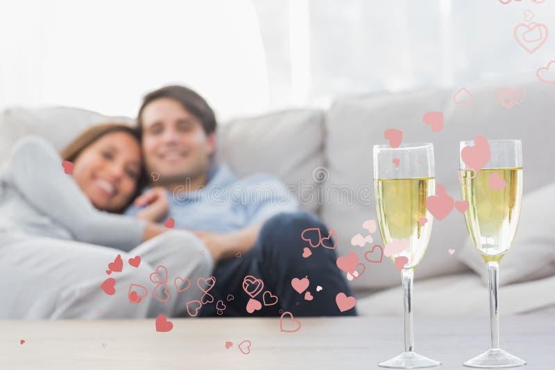 Imagen compuesta de los pares que descansan sobre un sofá con las flautas del champán ilustración del vector