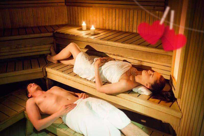Imagen compuesta de los pares que se relajan en la sauna fotos de archivo