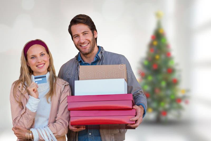 Imagen compuesta de los pares sonrientes que muestran la tarjeta de crédito y que llevan las cajas fotos de archivo libres de regalías