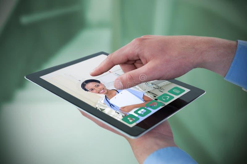 Imagen compuesta de manos croped del hombre de negocios usando la tableta digital imagen de archivo