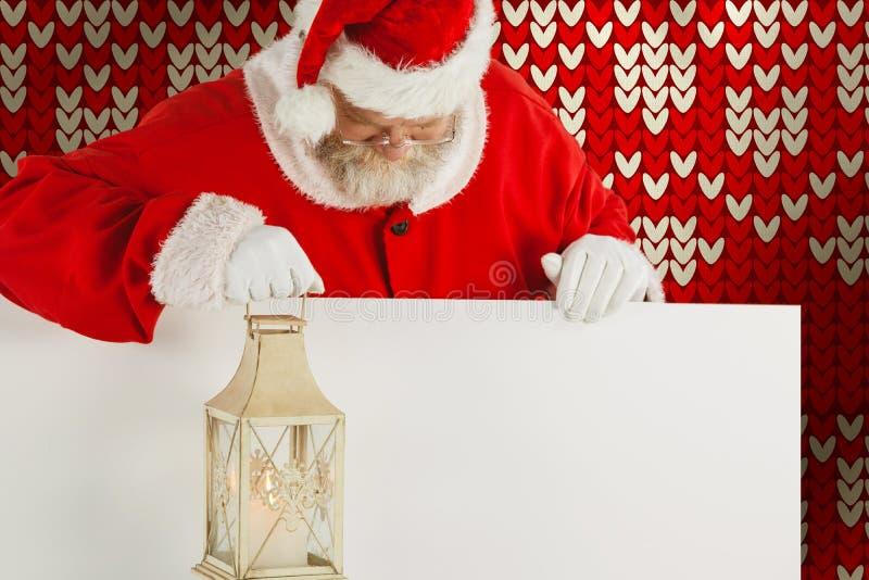 Imagen compuesta de Papá Noel que sostiene la linterna de la Navidad en el tablero blanco fotografía de archivo