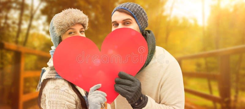 Imagen compuesta de pares jovenes atractivos en la ropa caliente que lleva a cabo el corazón rojo fotografía de archivo