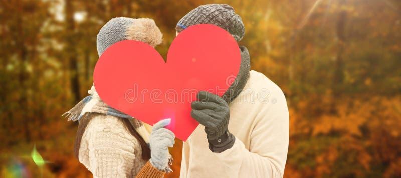 Imagen compuesta de pares jovenes atractivos en la ropa caliente que lleva a cabo el corazón rojo fotos de archivo libres de regalías