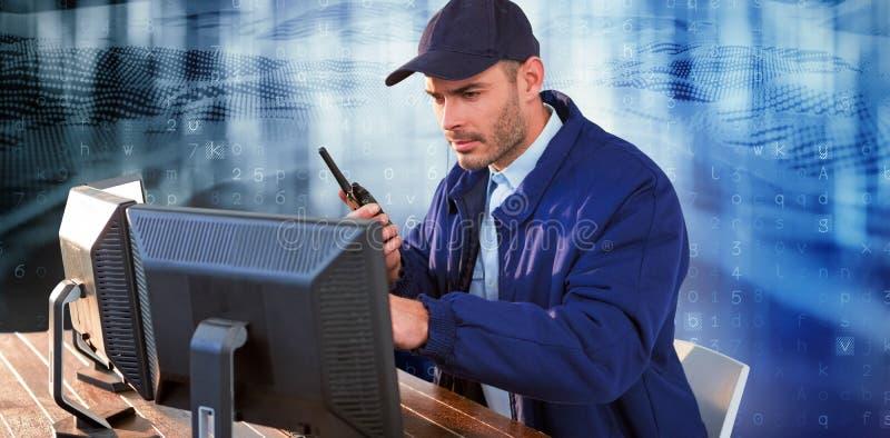 Imagen compuesta del agente de seguridad enfocado que mira observando los monitores de computadora y hablando en walki fotografía de archivo