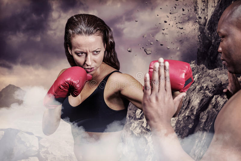 Imagen compuesta del boxeador de sexo femenino que practica con el instructor imagen de archivo libre de regalías