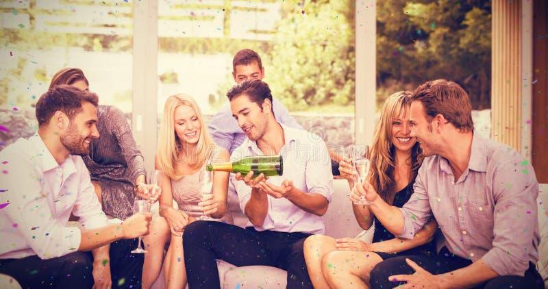 Imagen compuesta del champán de colada del hombre en la flauta para los amigos imágenes de archivo libres de regalías