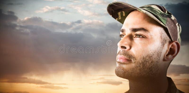 Imagen compuesta del cierre encima del casquillo que lleva del soldado confiado fotografía de archivo libre de regalías