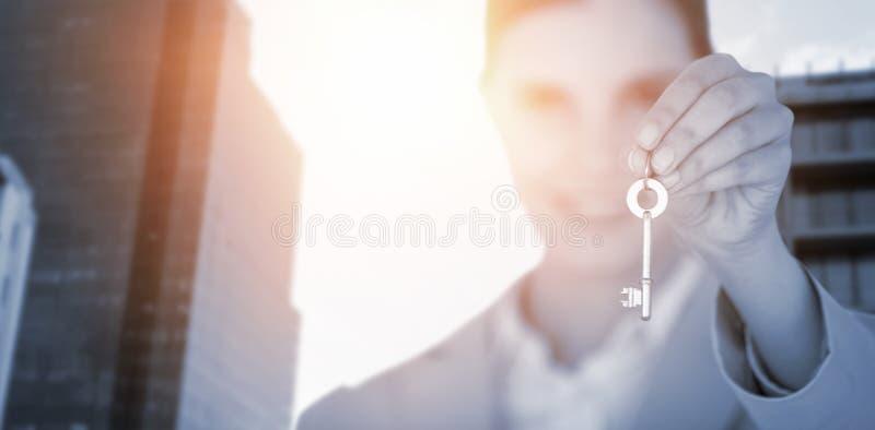 Imagen compuesta del cierre para arriba de la empresaria que muestra llave de la nueva casa fotos de archivo