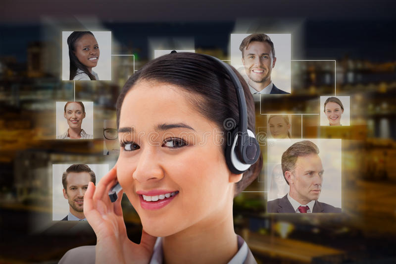 Imagen compuesta del cierre para arriba de un operador sonriente que presenta con auriculares fotos de archivo libres de regalías