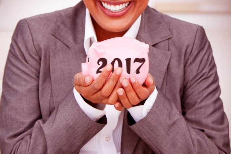 Imagen compuesta del cierre para arriba de una empresaria sonriente que lleva a cabo un piggybank fotos de archivo