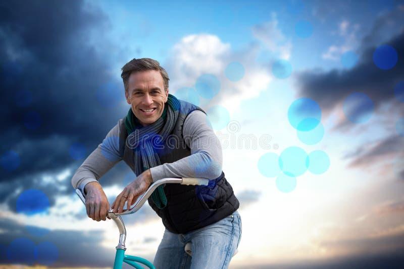 Imagen compuesta del compuesto digital del hombre hermoso en un paseo de la bici imagen de archivo libre de regalías