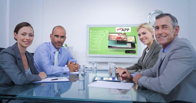 Imagen compuesta del equipo del negocio que mira la pantalla blanca foto de archivo