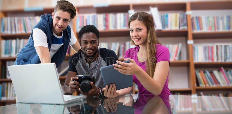 Imagen compuesta del equipo joven creativo del negocio que mira la tableta digital imagen de archivo