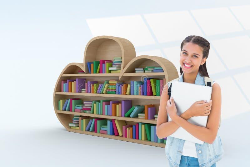 Imagen compuesta del estudiante que sostiene el ordenador portátil foto de archivo libre de regalías