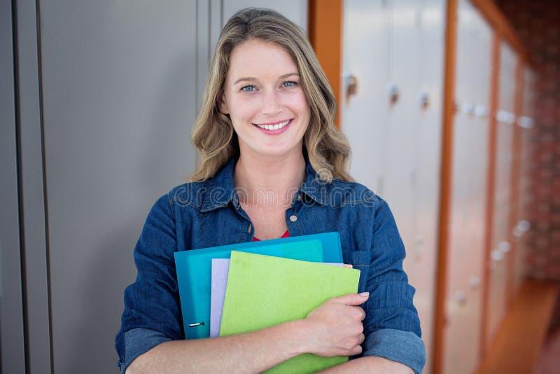 Imagen compuesta del estudiante sonriente que sostiene el cuaderno y el fichero imagen de archivo libre de regalías