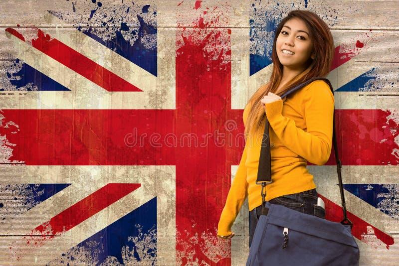 Imagen compuesta del estudiante universitario de sexo femenino con el bolso en parque imágenes de archivo libres de regalías