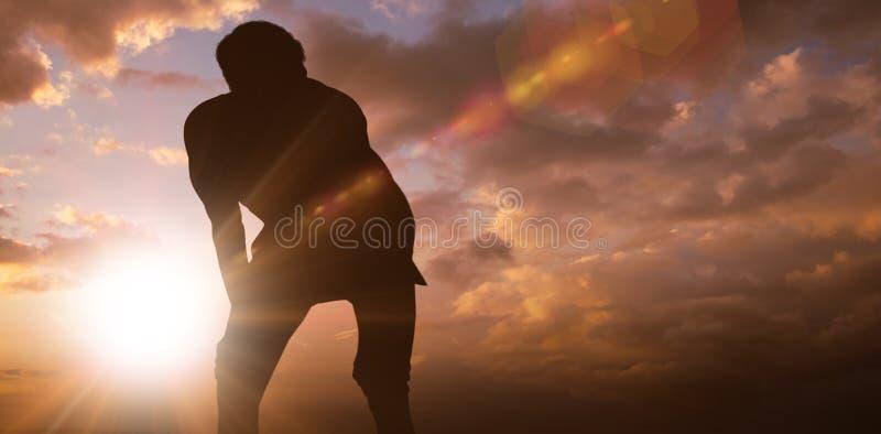 Imagen compuesta del hombre atlético que descansa con las manos en rodillas fotografía de archivo