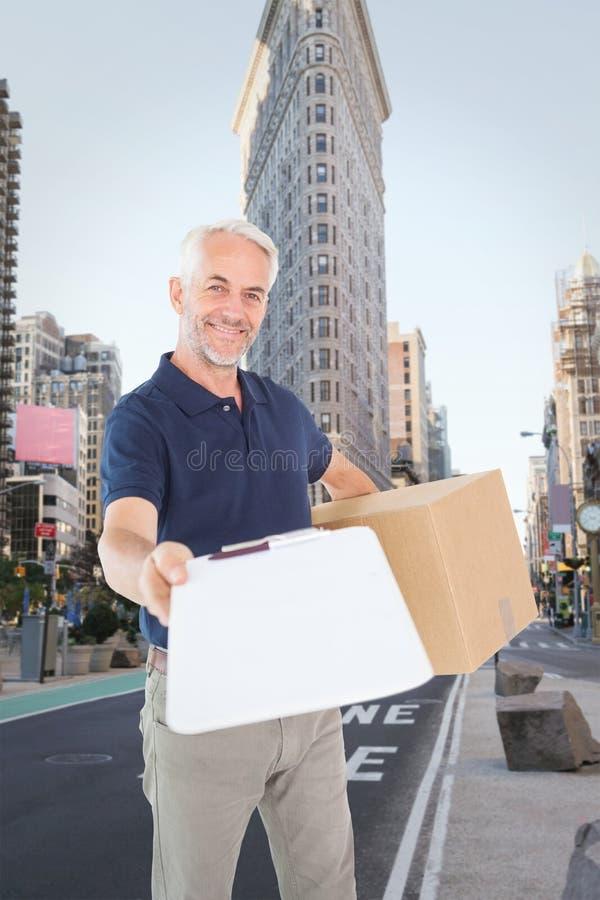 Imagen compuesta del hombre de entrega feliz que sostiene la caja de cartón y el tablero imagen de archivo libre de regalías