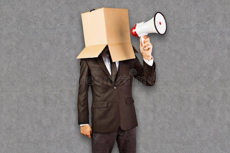 Imagen compuesta del hombre de negocios anónimo que sostiene un megáfono fotografía de archivo