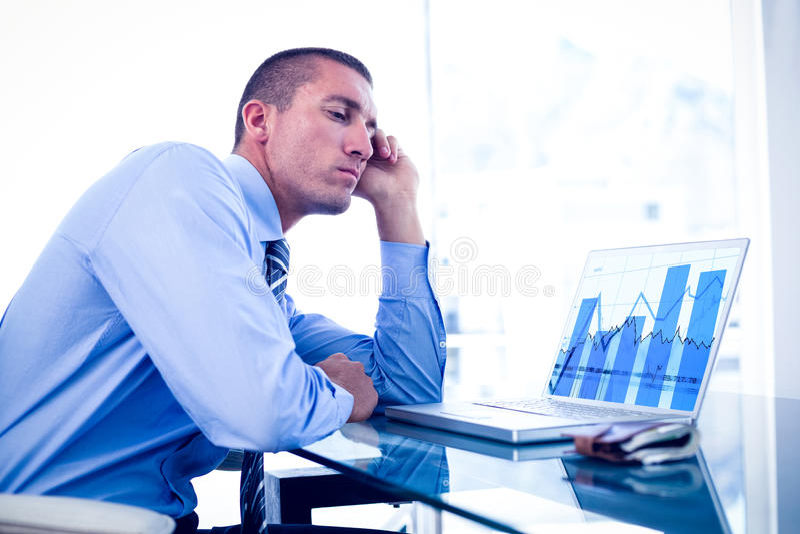 Imagen compuesta del hombre de negocios cansado que mira su ordenador portátil foto de archivo