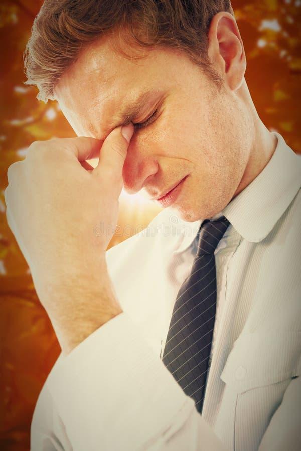 Imagen compuesta del hombre de negocios con un dolor de cabeza foto de archivo