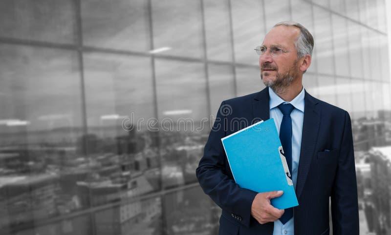 Imagen compuesta del hombre de negocios maduro pensativo que sostiene el fichero azul imágenes de archivo libres de regalías