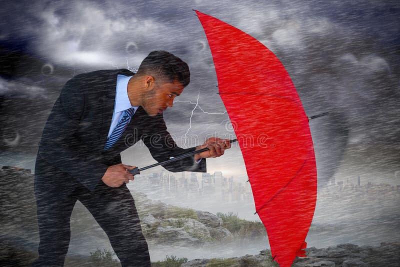 Imagen compuesta del hombre de negocios que defiende con el paraguas rojo foto de archivo libre de regalías