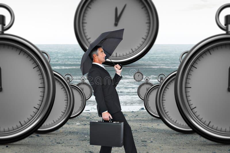 Imagen compuesta del hombre de negocios que empuja el viento con el paraguas fotografía de archivo libre de regalías